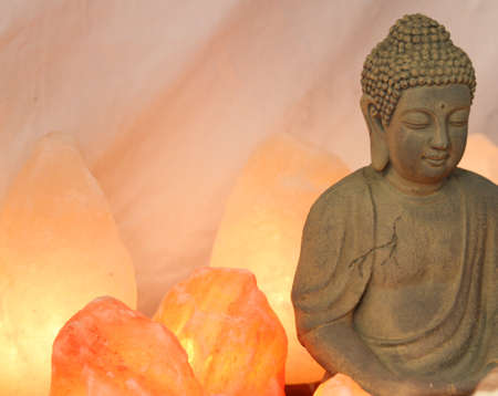 salt lamp: statuette of Buddha in prayer with salt lamps lit during the meditation of the disciples Stock Photo