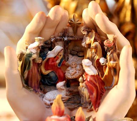 baby jesus: crib with the Nativity set and baby Jesus in the hands at Christmas Stock Photo