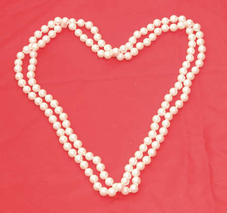 Pearl Necklace in the shape of a heart with red background 2 photo