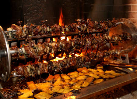 birds and roasts on a spit in the fireplace with a lot of polenta
