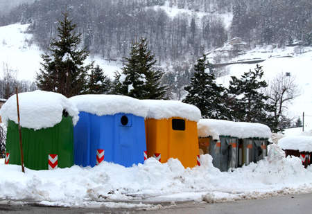 rubbish bins and bins for separate waste collection in a mountain town with snow photo
