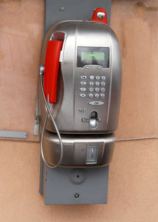 very old coin-operated italian phone with phone booth