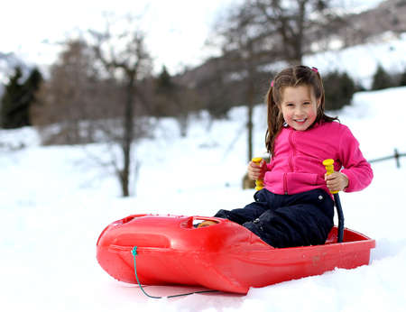 Pretty little girl with ski suitwith the bob on snowy mountain photo