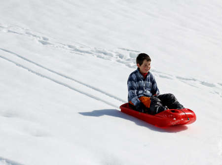 reckless: reckless kid down the descent with red bob on white snow in the mountains Stock Photo