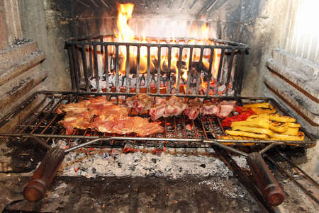 large fire in the fireplace to cook meat and vegetables and peppers with polenta