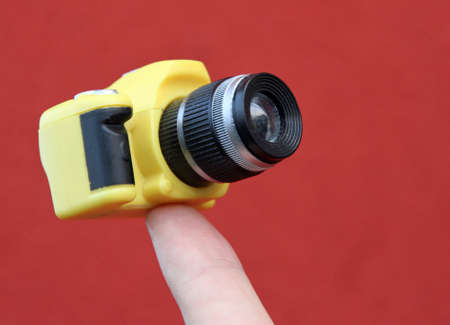tiny lenses: index finger holding a small yellow suspended camera and red background