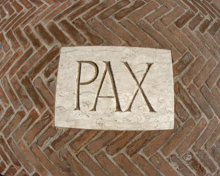 inscription PAX as a symbol of peace on a plaque in the midst of bricks  photo