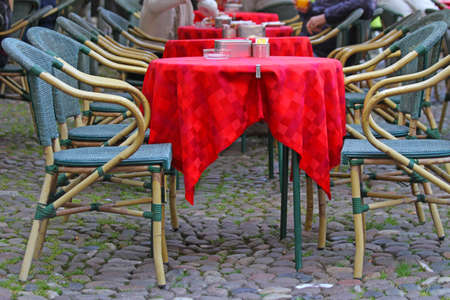 red tablecloth: Red tablecloth over the tables of a cafe to open in a famous European city