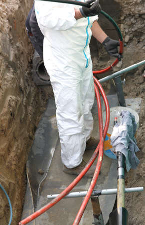 expert electrician in road excavation during the repair job of a large high voltage power cable photo
