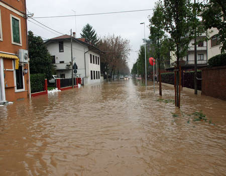 mud River invades the road completely submerged during the flood in the city Imagens - 27243805