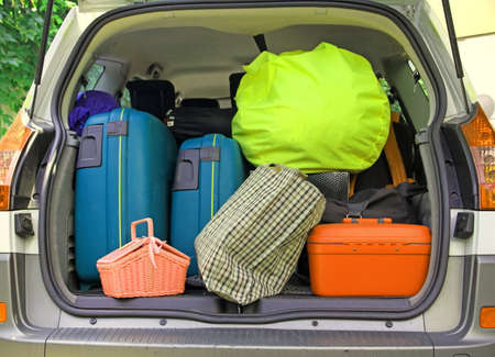 depart: twosuitcases and many bags in the trunk of the car ready to depart