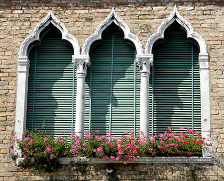 flowery balcony in Venetian style with arched windows of a historic  residence in Venice photo