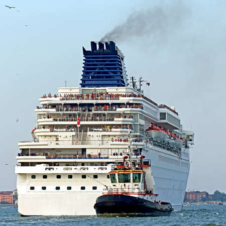 manoeuvre: Powerful tugboat while accurately manoeuvre the cruise ship out of the port city Stock Photo