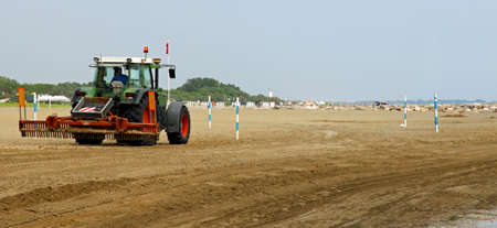 lido: tractor cleans the beach after a storm before the arrival of tourists