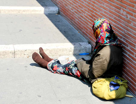 marginalized: very ancient Gypsy with lurid clothes while begging on the road
