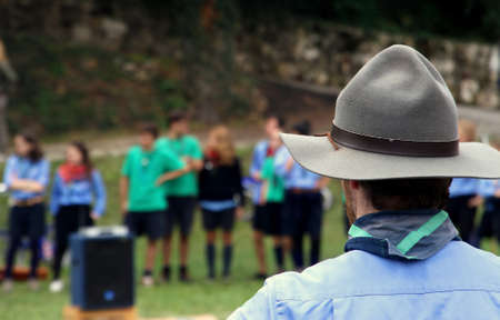 Chief scout with the typical Hat while controlling their kids to camp photo