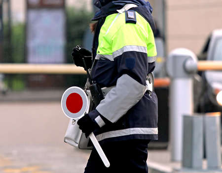 traffic warden: policewoman with the paddle while directing traffic