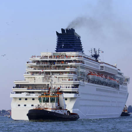manoeuvre: tugboat while accurately manoeuvre the cruise ship out of the port city Stock Photo