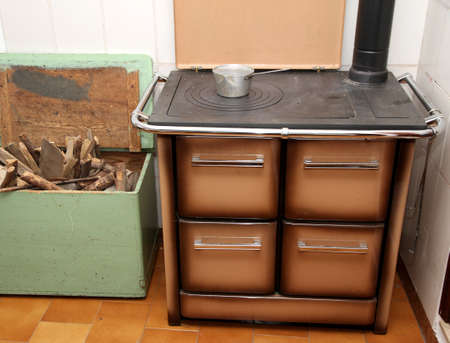 tiled stove: antique wood burning stove in a kitchen of a lovely mountain home 1