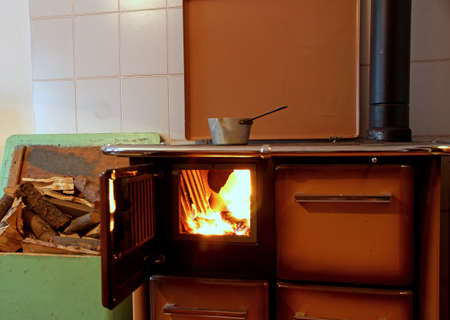 tiled stove: antique wood burning stove in a kitchen of a mountain home with a pot on the fire 2