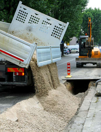 truck tipper during the emptying of the gravel road during the excavation work of laying of optical fibre conduits and electric cables