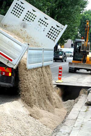 truck tipper during the emptying of the gravel road during the excavation work of laying of optical fibre conduits gas pipes Stock Photo