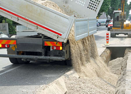 queasy: truck tipper during the emptying of the gravel road during the excavation work