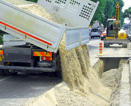 queasy: truck in the excavation after laying of underground electric cables and telecom cables optical fibre Stock Photo