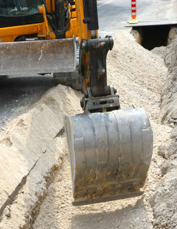 fiberoptic: big bucket of a bulldozer during the digging in the road in the city