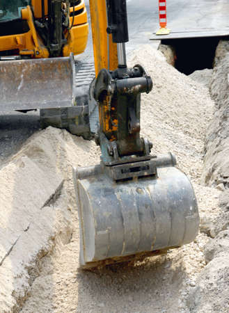 big bucket of a bulldozer during the digging in the road in the city