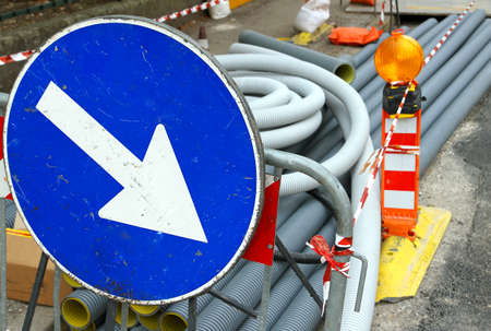 fiberoptic: big blue sign with white arrow during excavation work on the street in the city Stock Photo