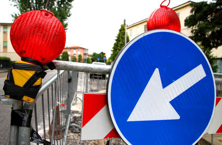 delimit: red signal lamps and a huge road sign to delimit the roadworks in the city