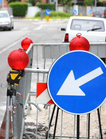 roadwork: narrowing of the roadway with red signal lamps and a road sign to delimit the roadworks in the city