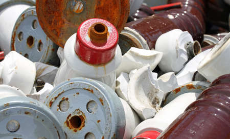 insulators: pieces of iron and ceramic Electrical insulators in an industrial waste landfill