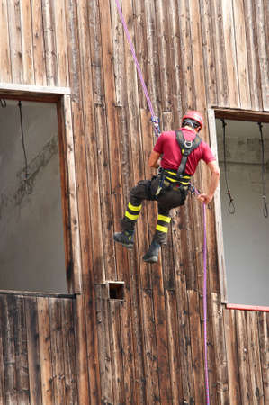 abseiling: expert firefighter climber down into the wall of the House in abseiling