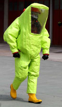 riesgo quimico: persona con traje de radiaci�n botas de goma amarillas y amarillas contra para protegerse contra el riesgo de ataque biol�gico bacteriol�gica y qu�mica