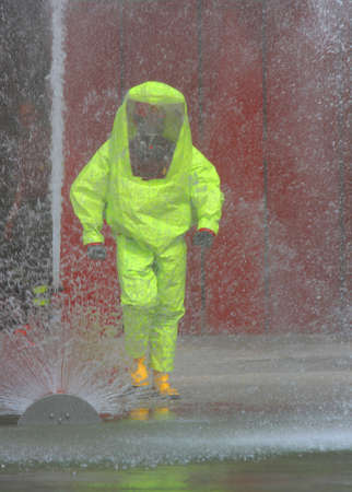 man with the yellow jumpsuit and the fire hydrant in action during a fire drill photo