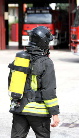 firefighter with yellow  oxygen cylinder and the helmet walks towards the fire photo