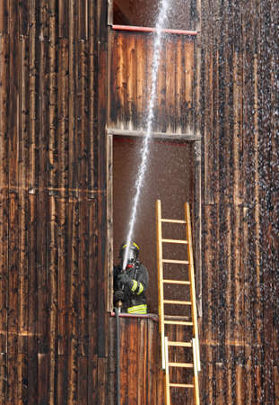 Firefighter with hydrant in action when switching off a fire during exercises in the Firehouse Stock Photo