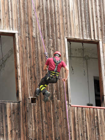abseiling: brave fireman climber expert you haul in the wall of the House abseiling during an exercise