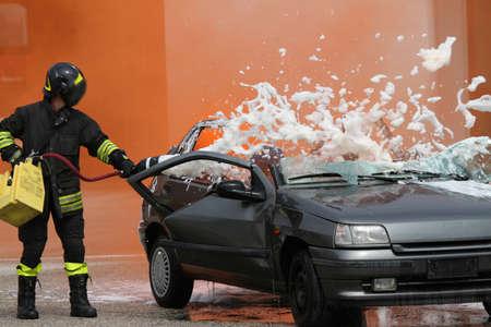 espumante: Bombero con la m�scara del fuego con la m�quina de formaci�n de espuma