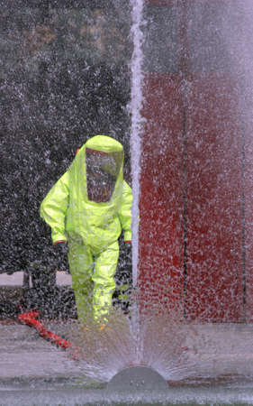 jet of water to wash the yellow suit used during an exercise of biohazard contamination Stockfoto