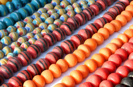 lines of colored pearl necklaces of African handicrafts for sale at flea market photo