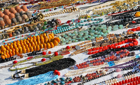 many handmade necklace of beads or wood for sale in African products stall at flea market photo