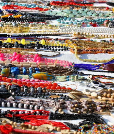 many handmade necklace of beads for sale in African products stall at flea market in italy photo