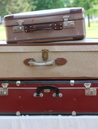 three old suitcases, one above the other in the market for vintage and retro stuff photo