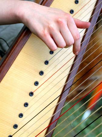 ハープの弦を摘採しながらきれいな女の手 写真素材