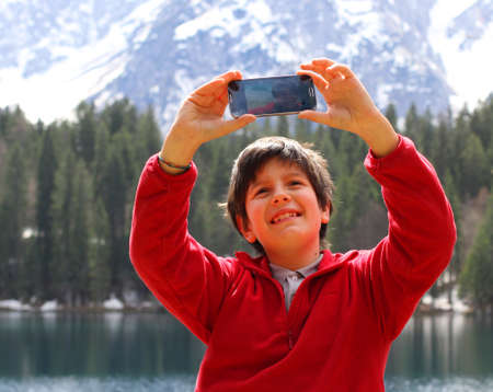 smiling boy while taking a picture with smartphone photo