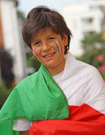 Young boy with painted flag before the football match