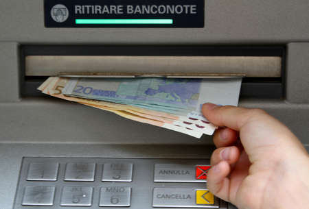 Withdraw money in banknotes from an ATM in Italy Stock Photo - 29423761